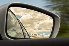 Rear View Mirror. Rear / side view mirror reflecting clouds & sky w/ motion blur Stock Image
