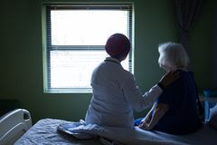 Female doctor and senior woman looking outside through the window. Rear view of a mixed race female doctor and a senior Caucasian woman sitting on a bed and stock images