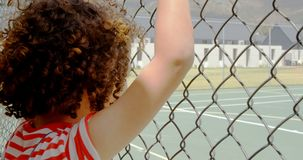 Rear view of mixed-race schoolgirl standing near wire mesh fence at school 4k stock video footage