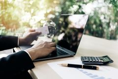 Rear view of modern businessman hands holding credit card typing numbers on computer keyboard while sitting with pen, Royalty Free Stock Photos
