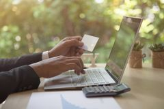 Rear view of modern businessman hands holding credit card typing numbers on computer keyboard while sitting with pen, Royalty Free Stock Images