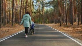 Mom teaches little son to ride a balance bike on the road. Rear view: Mom teaches little son to ride a balance bike on the road in a pine park, slow-motion shot stock video