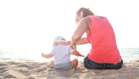 Rear view of mother and baby boy sitting. On the sandy beach royalty free stock photos