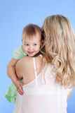 Rear view of mother with child over shoulder. Rear view of mother with cute baby girl looking over shoulder Royalty Free Stock Photos