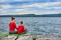 Rear view of the mother and daughter are practicing yoga on the rock near river. Beautiful young mother and little daughter in the sportwear and barefoot Royalty Free Stock Images