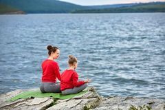 Rear view of the mother and daughter are practicing yoga on the rock near river. Royalty Free Stock Photo