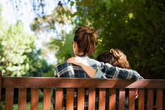 Rear view of mother and daughter sitting with arms around on wooden bench Stock Photo