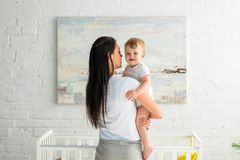 Rear view of mother holding cute smiling baby in hands. At home stock photo