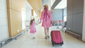 Rear view of mother and little daughter holding hands walking to the waiting room in airport stock footage