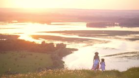 Rear view of mother and little daughter holding hands walks down the hill with perfect view on the river at sunset stock footage