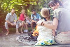 Rear view of mother sitting with arm around daughter while camping at park stock image