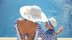 Woman in white hat with bow and little boy sitting at edge of swimming pool together