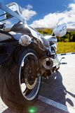 Rear view on motorcicle against blue sky. Exhaust pipe, rear brake and wheel of motorcicle. Shallow focus, sun glare, backlight stock photography