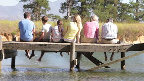Rear View Of Multi-Generation Family Sitting On Jetty stock footage