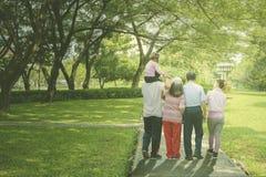 Multi generation family walks in the park stock photo