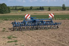 Rear view of a multi-purpose, farm tractor pulled harrow for aerating fields, spreading straw, cultivating stubble and fighting we. Eds Stock Photo