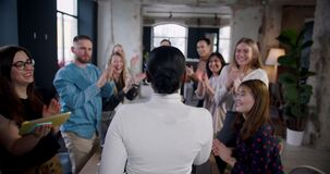 Rear view multiethnic business people raise to applause to successful African boss woman at loft office slow motion.
