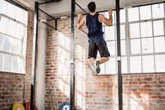 Rear view of muscular man doing pull ups. At the gym Royalty Free Stock Photo