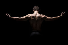 Rear view of muscular man with his arms stretched out Royalty Free Stock Photos