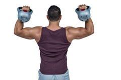 Rear view of a muscular man lifting kettlebells Stock Photography