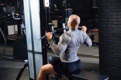 Rear view, muscular man playing sports in a gym. Strong guy is training his back.  royalty free stock photos