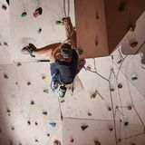 Rear view muscular man practicing rock-climbing on rock wall indoors stock photography