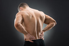 Rear View Of Muscular Man Suffering From Backache. Standing against black background Royalty Free Stock Photo