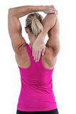 Rear view of muscular woman stretching her arm Royalty Free Stock Photos