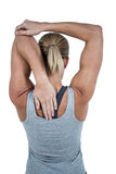 Rear view of muscular woman stretching her arm Stock Image