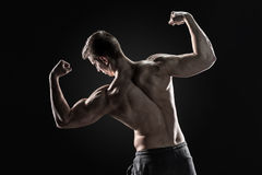 Rear view of muscular young man showing back, biceps muscles Royalty Free Stock Photos