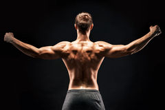 Rear view of muscular young man showing back, biceps muscles Royalty Free Stock Photo