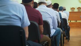 Rear view of muslim men in skullcaps sitting at the mass rally