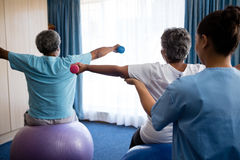 Rear view of nurse training seniors in lifting dumbbells Stock Photography