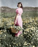 Rear View Of A Girl Standing In A Meadow Holding A Flower Basket And Smiling Stock Image