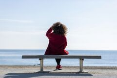 Free Rear View Of A Young Curly Woman Wearing Red Denim Jacket Sitting On A Bench While Looking Away To Horizon Over Sea Royalty Free Stock Images - 172934729