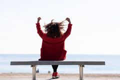 Free Rear View Of A Young Curly Woman Wearing Red Denim Jacket Sitting On A Bench While Looking Away To Horizon Over Sea Stock Photography - 199780072