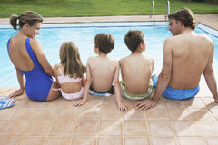 Rear View Of Family Sitting By Pool Royalty Free Stock Photos