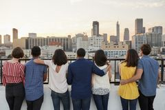 Rear View Of Friends Gathered On Rooftop Terrace Looking Out Over City Skyline Royalty Free Stock Photos