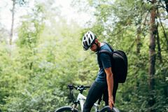 Free Rear View Of Male Cyclist Cycling On Mountain Road On A Sunny Day. Professional Cyclist Riding A Bike In The Forest Outdoor Royalty Free Stock Image - 196215626