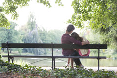Rear View Of Romantic Young Couple Sitting On Bench At Lakeside Stock Images