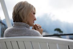 Free Rear View Of Thoughtful Woman Relaxing In Porch Stock Photos - 103595603