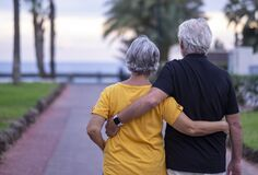 Free Rear View Of Two White-haired Senior People Walking Happy Enjoying Their Retirement And Beach Vacation. Serene And In Love Couple Stock Photo - 204740560