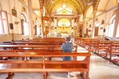Rear view of the old man kneeing and praying in Santa Cruz Church or Kudi Chin, one of the many old Catholic church in Bangkok. W stock photo