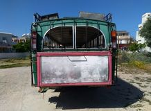 Rear view of an old rusting green painted bus with roof rack parked in a rustic location in cyprus. With surrounding buildings Royalty Free Stock Image