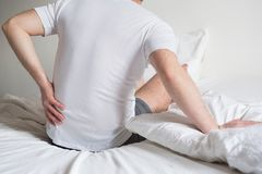Uncomfortable mattress and pillow causes neck pain. Rear view of one man sitting on bed having back pain Stock Photos