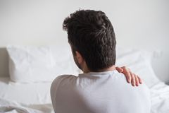 Uncomfortable mattress and pillow causes neck pain. Rear view of one man sitting on bed having back pain Stock Photo