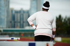 Sporty girl. Rear view of over-size woman with bottle of water moving on stadium after training Stock Photography