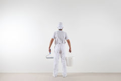 Rear view of painter man looking at blank wall, with paint rolle. R and bucket, isolated on white room Royalty Free Stock Image