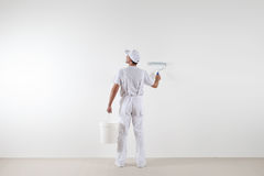 Rear view of painter man looking at blank wall, with paint rolle. R and bucket, isolated on white room Royalty Free Stock Photo