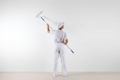 Rear view of painter man looking at blank wall, with paint roller stick, isolated on white room stock images